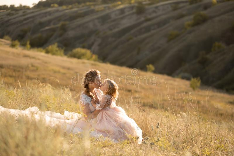 Young mother with a little daughter in pink dresses are sitting in the field. Mom hugs daughter, hugging her stock photo