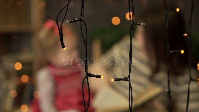 Young mother with little daughter reading book at home. Mom and little daughter playing on background of garlands. Blur royalty free stock photography