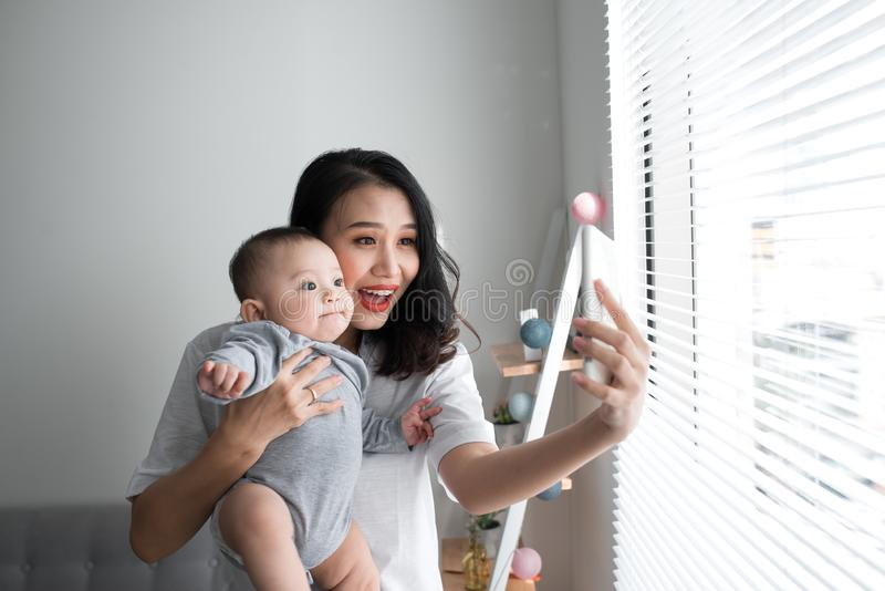 Young mother with little daughter taking selfie near window at home stock photo