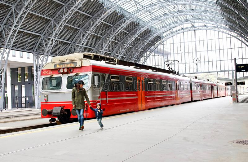 Young mother and little kid walk through the Bergen train station platforms with typical red Voss train on background, Bergen. stock image