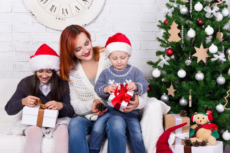 young mother and little kids with gift boxes in front of Christmas tree royalty free stock photography