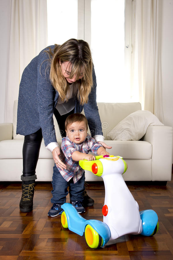 Young mother and little one year old son walking with baby walker taking his first brave steps stock photo
