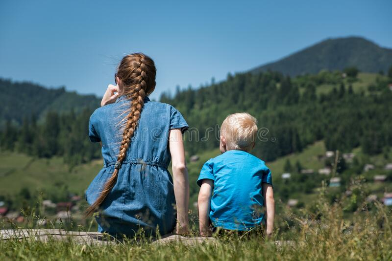 Young mother and little son in nature background nature. Countryside. Back view stock photo