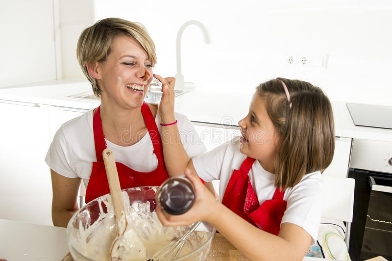 Young mother and little sweet daughter in cook apron cooking together baking at home kitchen stock images