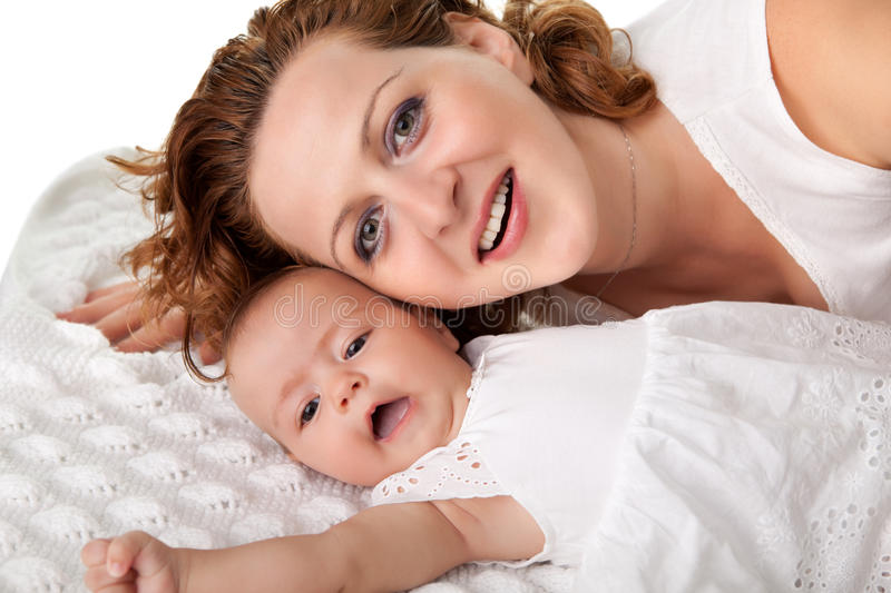 Young mother lying on bed with her baby stock photography