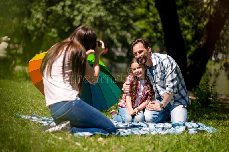 Young Mother Making Photo Of Husband And Daughter In The Park. Father Is Hugging His Daughter While Sitting On The stock images