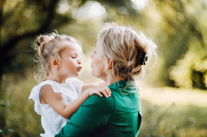 Young mother in nature holding small daughter in the arms. Beautiful young mother in green sunny summer nature holding her cute small daughter in the arms stock photo