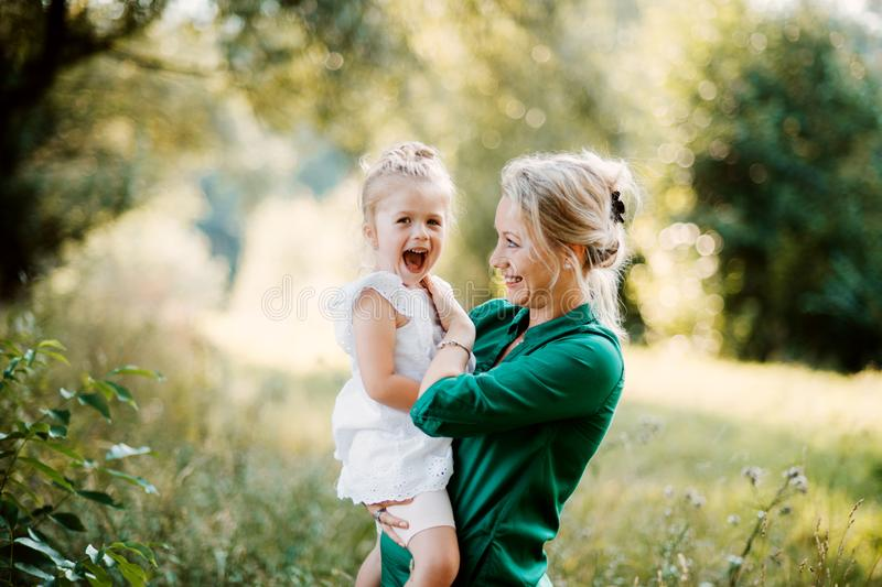 Young mother in nature holding small daughter in the arms. Beautiful young mother in green sunny summer nature holding her cute small daughter in the arms stock photos