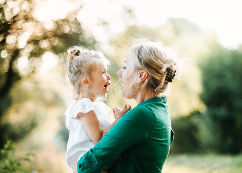 Young mother in nature holding small daughter in the arms. Beautiful young mother in green sunny summer nature holding her cute small daughter in the arms royalty free stock images