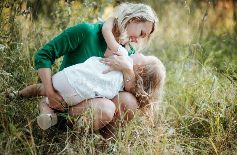 Young mother in nature holding small daughter in summer. Beautiful young mother in green sunny summer nature holding her cute small daughter stock photo