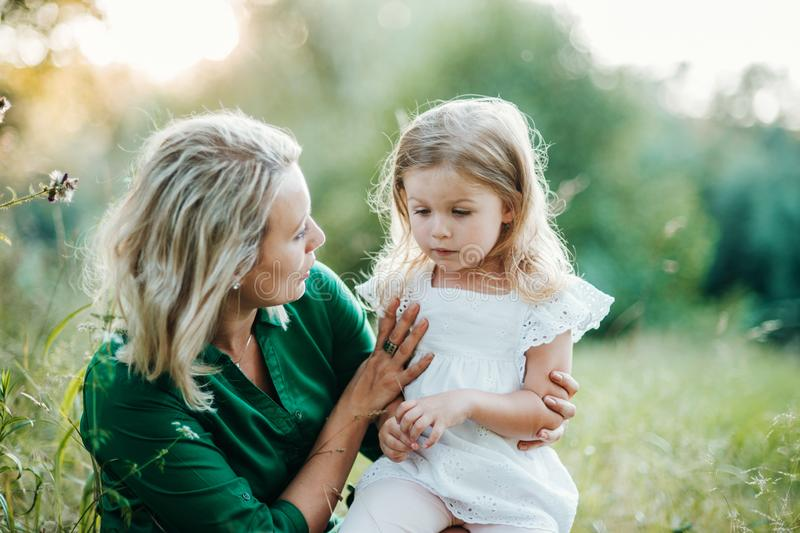 Young mother in nature holding small daughter in summer. Beautiful young mother in green sunny summer nature holding her cute small daughter royalty free stock photos