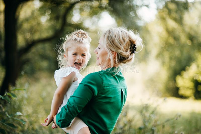 Young mother in nature with small daughter in the arms, having fun. Copy space. royalty free stock images