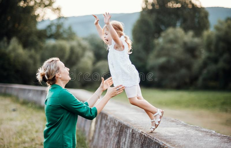 Young mother in nature with small daughter, having fun. A girl jumping into mother`s arms royalty free stock photos