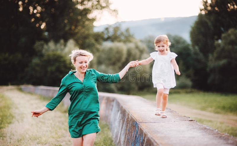 Young mother in nature with small daughter, having fun. A girl running on a concrete wall, holding hands stock photo