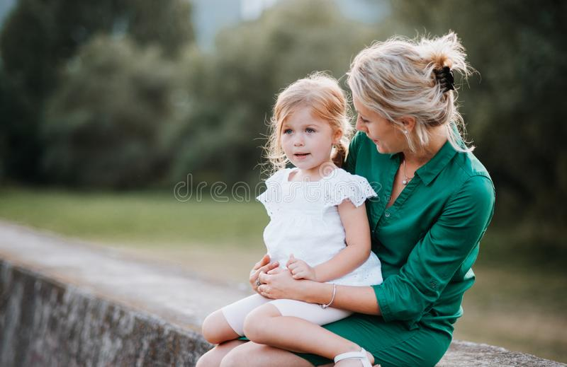 Young mother in nature with small daughter, sitting on a stone wall. A young mother in nature with small daughter, sitting on stone wall royalty free stock images