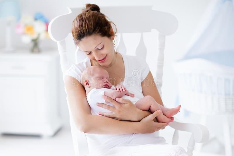 Young mother and newborn baby in white bedroom. Young mother holding her newborn child. Mom nursing baby. Woman and new born boy relax in a white bedroom with stock images