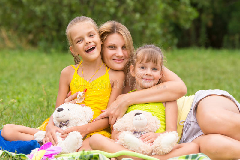 Young mother on picnic hugging two daughters, five and seven years royalty free stock image