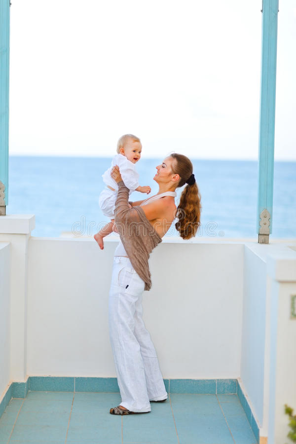 Young mother playing with baby on balcony royalty free stock photography