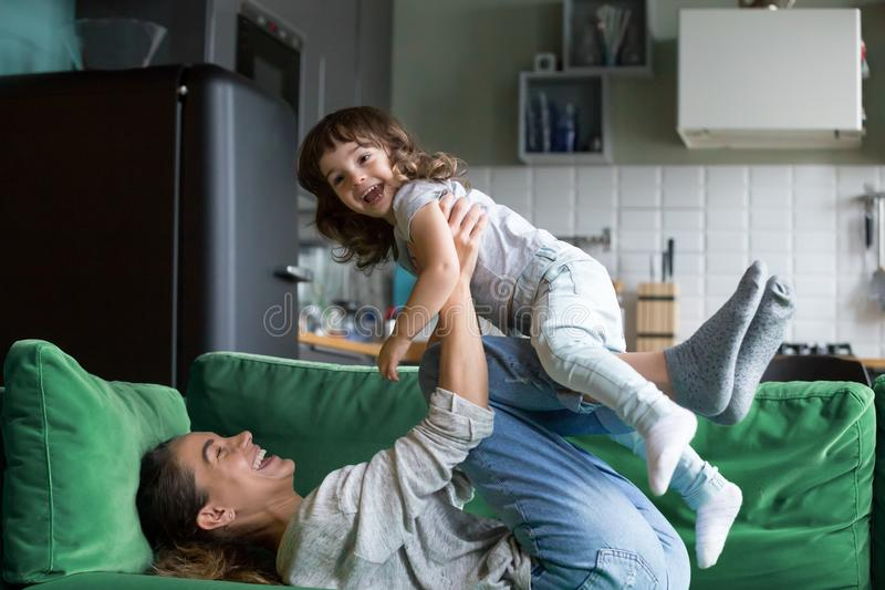 Happy mother playing having fun with kid daughter on sofa. Young mother playing with cute baby girl on sofa at home, happy single mom or sister laughing lifting royalty free stock photography