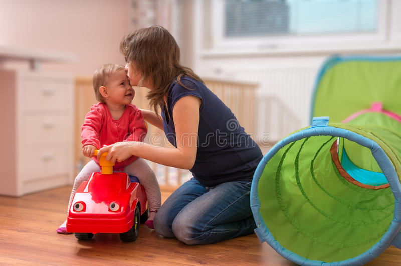 Young mother is playing with daughter. Woman is teaching her child to drive toy car. royalty free stock photos