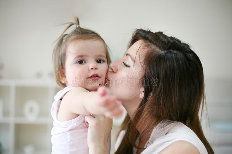 Young mother playing with her baby girl in bed. Mother kissing royalty free stock image