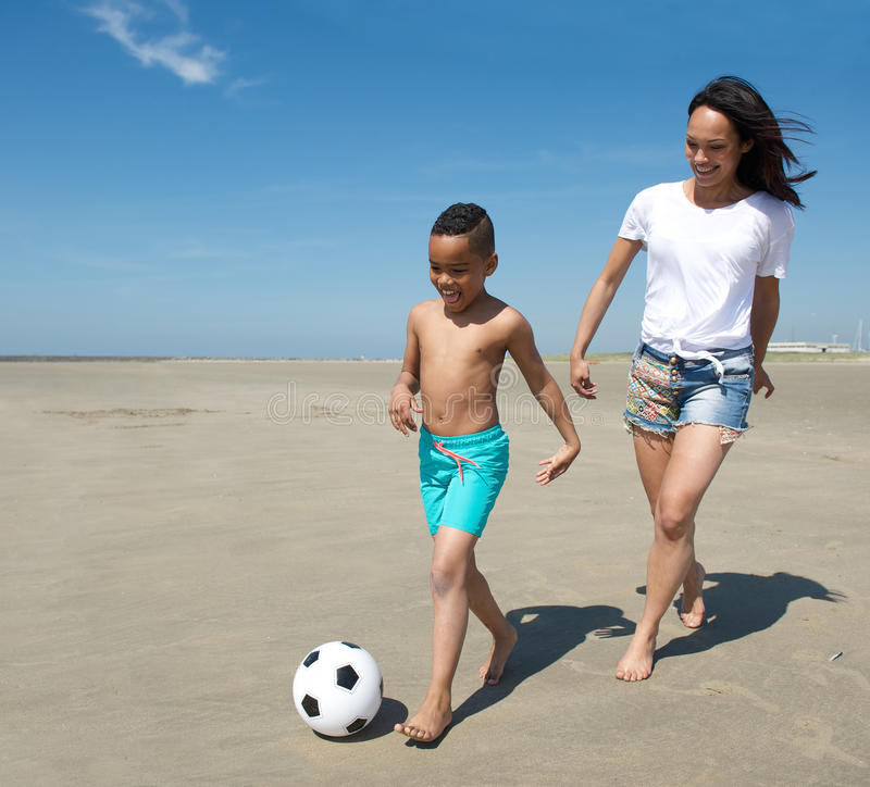Young mother playing with son on the beach. In summer stock photography