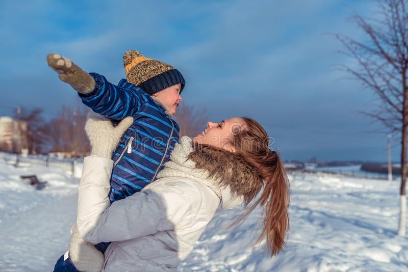 A young mother plays with baby boy for 2-3 years in winter city. Happy smiling and looking each other. A happy family royalty free stock image