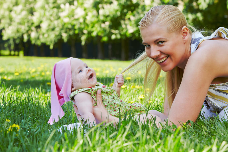 Young mother plays with baby on grass royalty free stock image