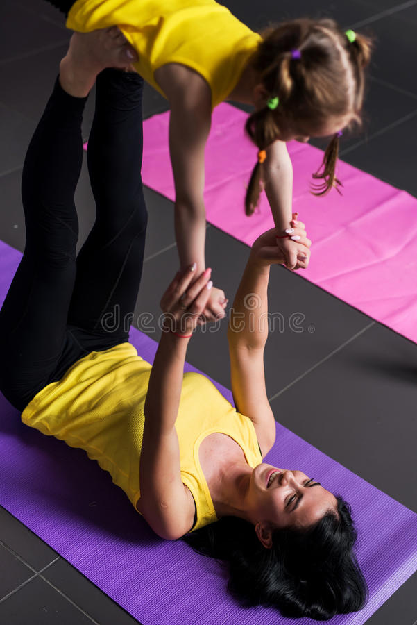 Young mother practicing yoga together with a school-age daughter doing flying warrior pose lying on mat royalty free stock photography