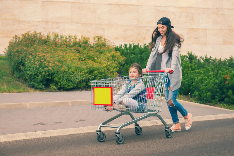 Young mother pushes her daughter in the shopping cart stock images