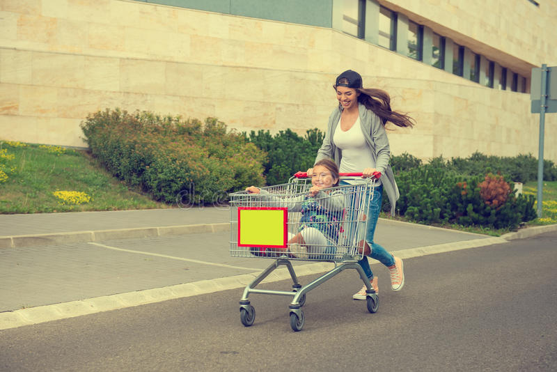 Young mother pushes her daughter in the shopping cart stock photos