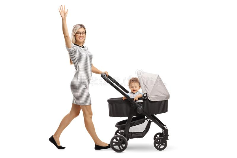 Young mother pushing a stroller with a baby and waving. Full length portrait of a young mother pushing a stroller with a baby and waving isolated on white stock photo