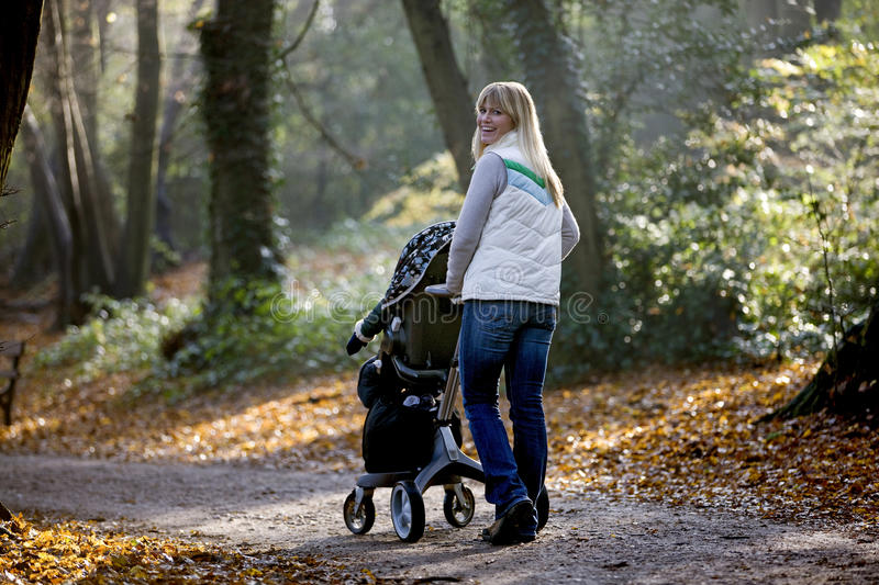 A young mother pushing a stroller in the park, smiling stock images