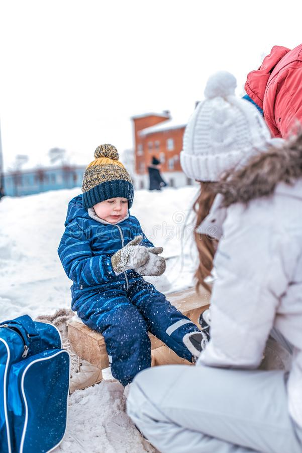 Young mother puts on skates in the winter on a public skating rink. Little boy in a blue jumpsuit, mittens in the snow stock photos
