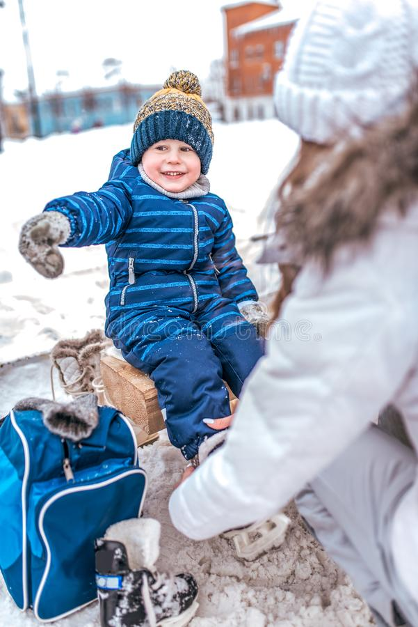 Young mother puts skates in winter public skating rink. The little boy happy smiling shows his hand to the side, in blue. Jumpsuit, mittens in snow. Learning stock photo