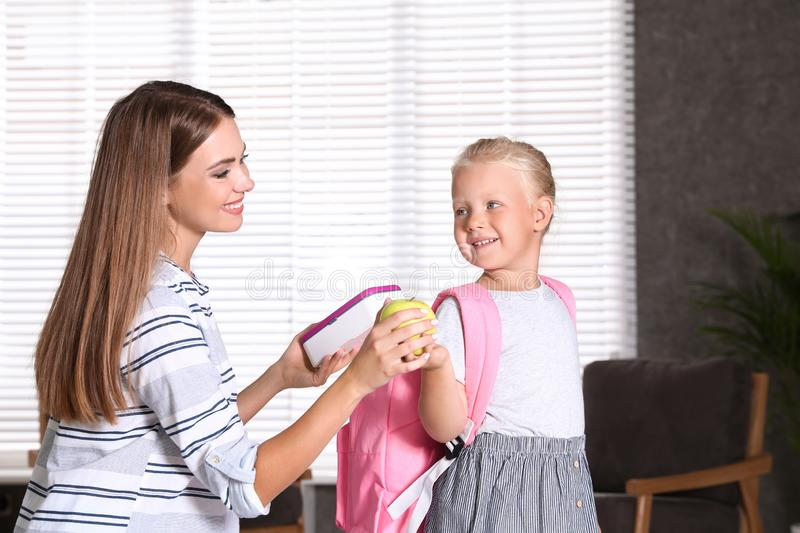 Young mother putting lunch into her little child`s school bag stock image
