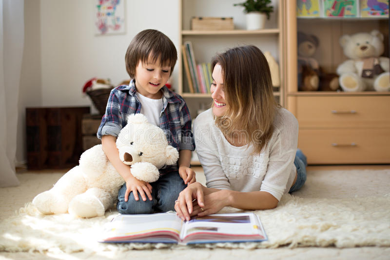 Young mother, read a book to her child, boy in the living room o stock photo