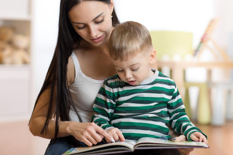 Young mother reads book to son. Cute little child boy and his mom. stock photos