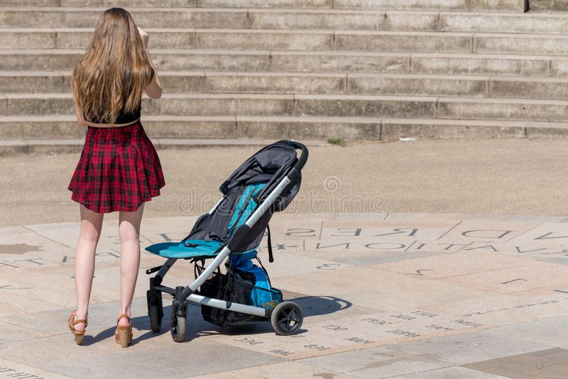 Isolated blonde girl with short skirt and baby buggy takes selfie in imposing setting royalty free stock photography