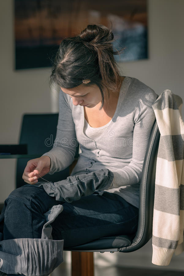 Young mother repairing clothes royalty free stock photos