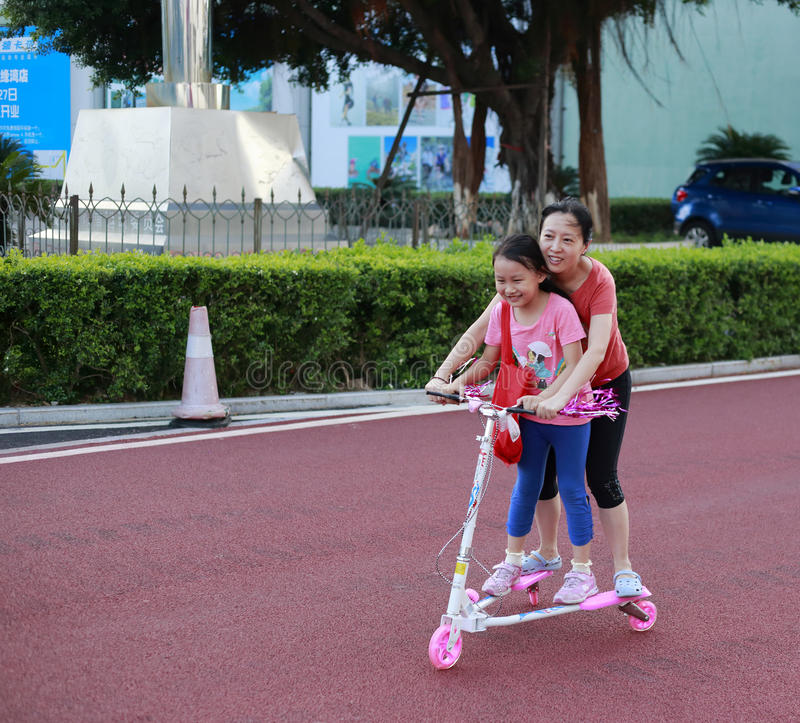 A young mother roller skating with her daughter stock photography