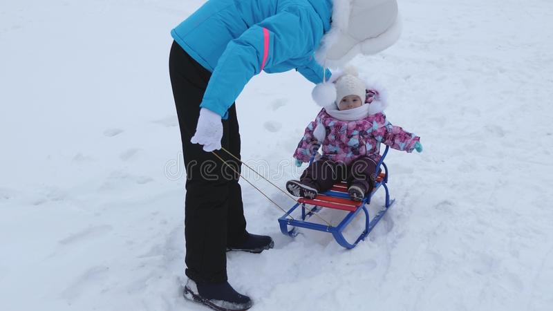 Young mother rolls little baby on sled along snowy road in winter. Child is naughty and cries while sitting in sled stock image