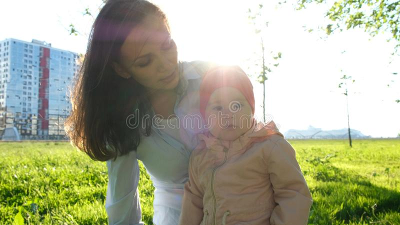 Young mother showing her child to the distance and explaining something. European family sitting in the park on the stock image