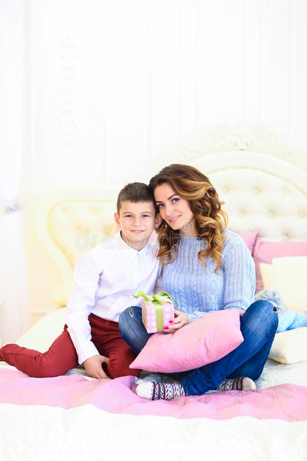 Young mother sitting with son and gift on bed. royalty free stock image
