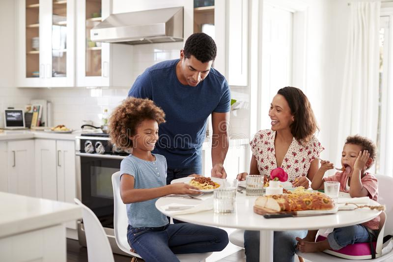 Young mother sitting at table in the kitchen with children, father serving them food, selective focus royalty free stock image