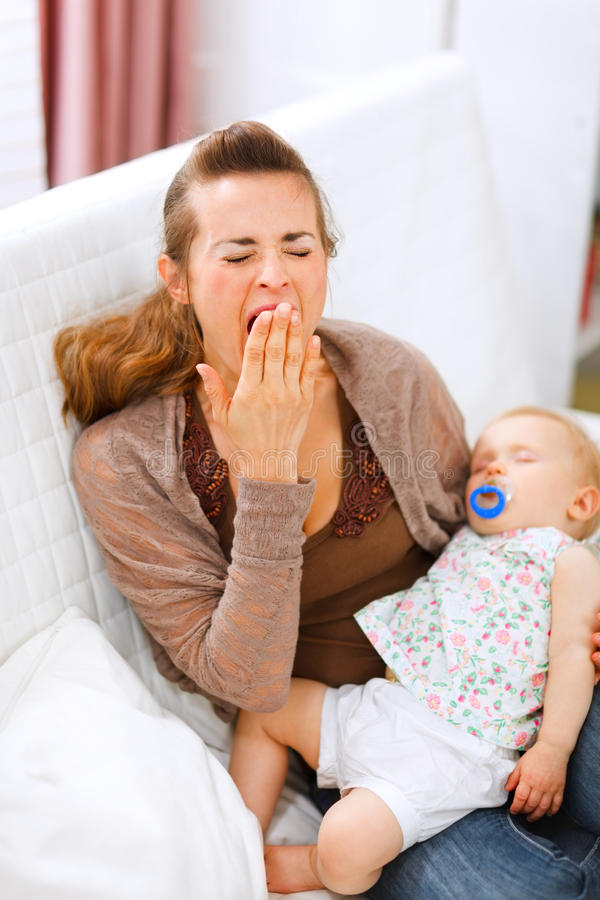 Young mother with sleeping baby on hands yawing. Mother with sleeping baby on hands yawing at home royalty free stock photo