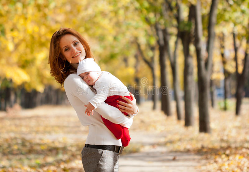 Young mother with sleeping child in autumn park. Happy young mother with sleeping child on hands walking in autumn park royalty free stock photography