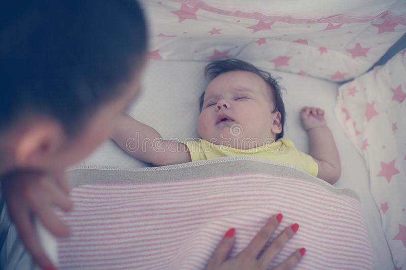 Young mother is sleeping her baby. From above royalty free stock image