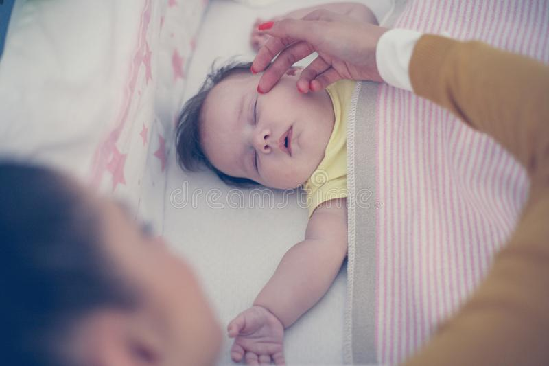 Young mother is sleeping her baby. Close up. From above royalty free stock photo