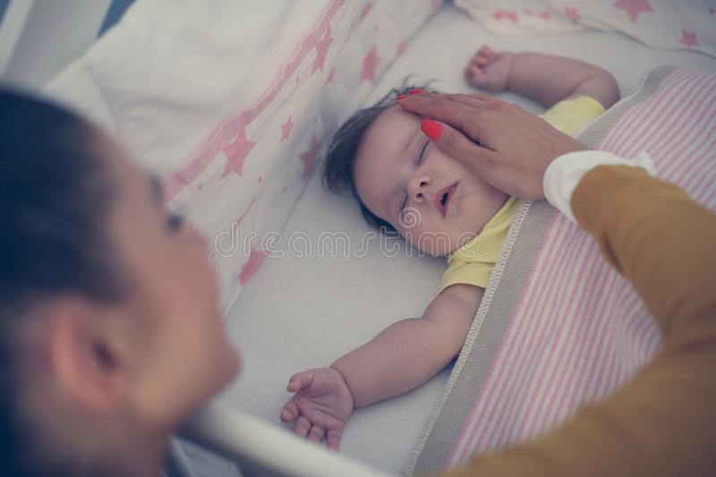 Young mother is sleeping her baby. Close up. Focus is on background royalty free stock image